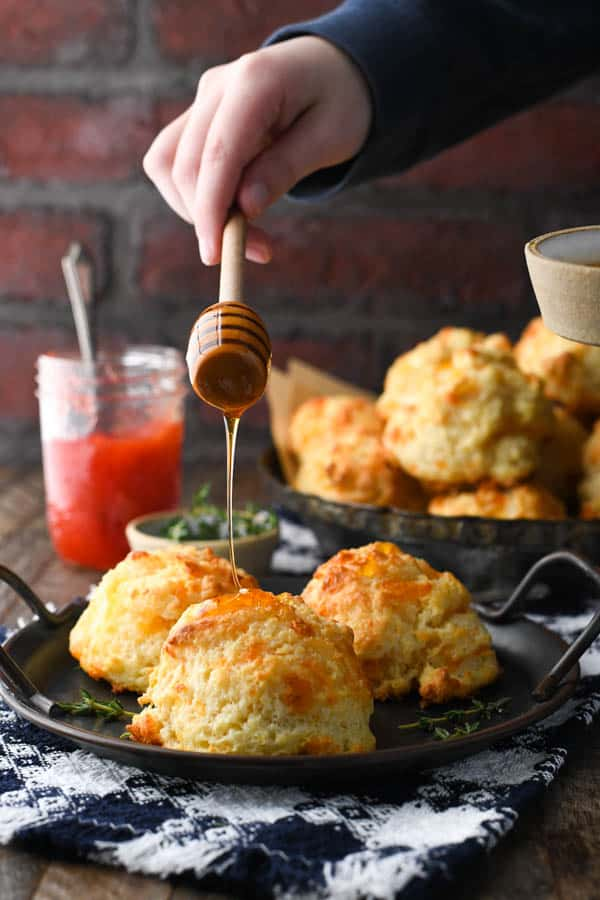 Drizzling honey over a plate of fluffy cheese biscuits