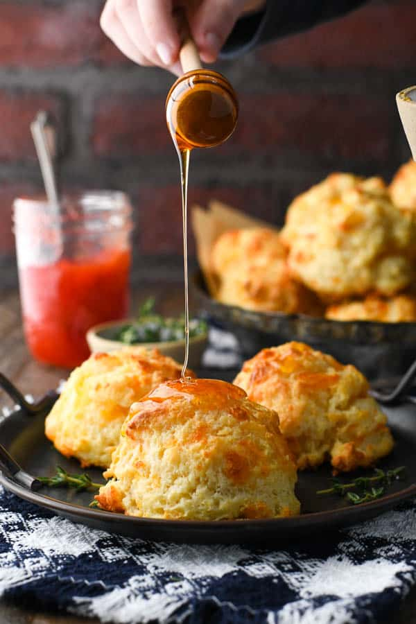 Drizzling honey on top of fluffy cheese biscuits