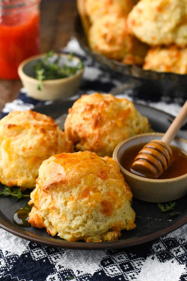 Side shot of a southern cheese biscuits recipe on a plate with honey