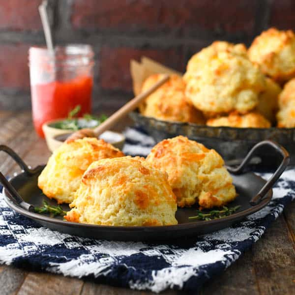 Square image of savory cheese drop biscuits on a plate