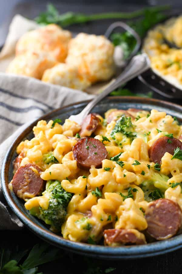 Close up side shot of a bowl of skillet mac and cheese with smoked sausage and broccoli