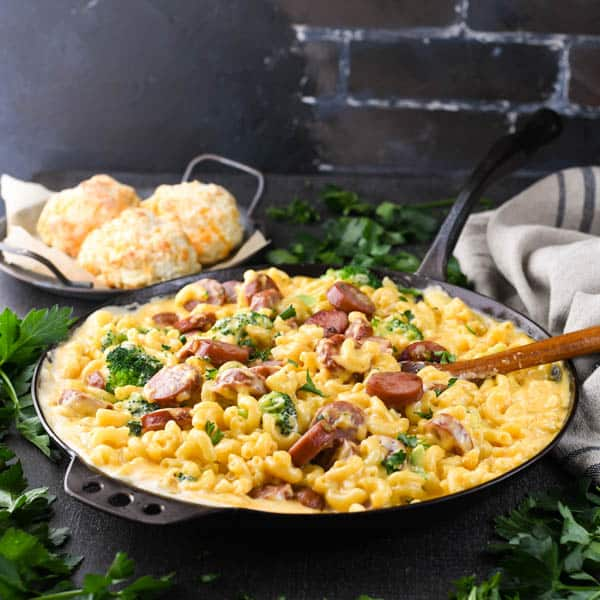 Square image of a smoked sausage pasta skillet with broccoli and cheese