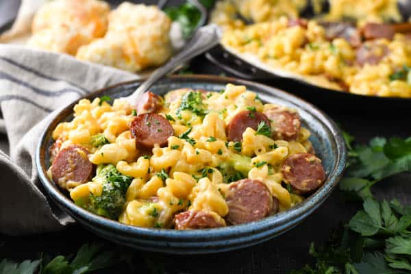 Horizontal image of a bowl of easy smoked sausage pasta with broccoli and biscuits on the side