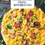Overhead shot of cheesy smoked sausage pasta in a skillet with text title overlay