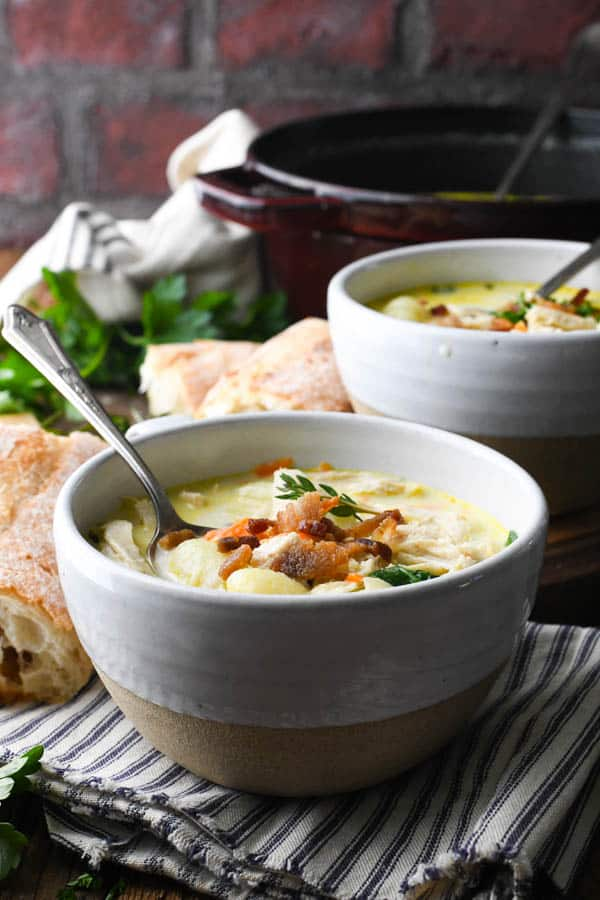Two bowls of creamy chicken gnocchi soup on a table in front of a brick wall