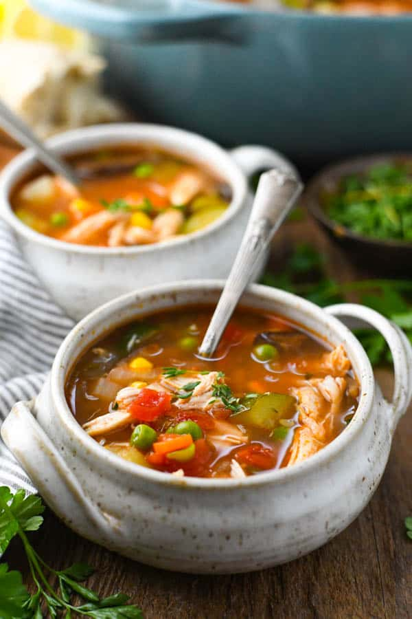 Front shot of two bowls of a hearty chicken vegetable soup recipe served on a wooden table