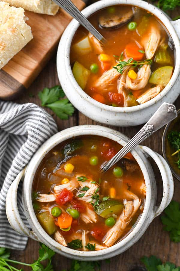 Overhead shot of two bowls of old fashioned chicken vegetable soup recipe served with baguette
