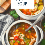 Homemade chicken vegetable soup in two bowls on a wooden table with text title overlay