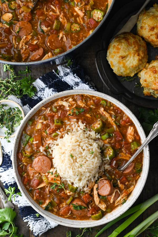 Overhead image of chicken and sausage gumbo with okra and a side of biscuits