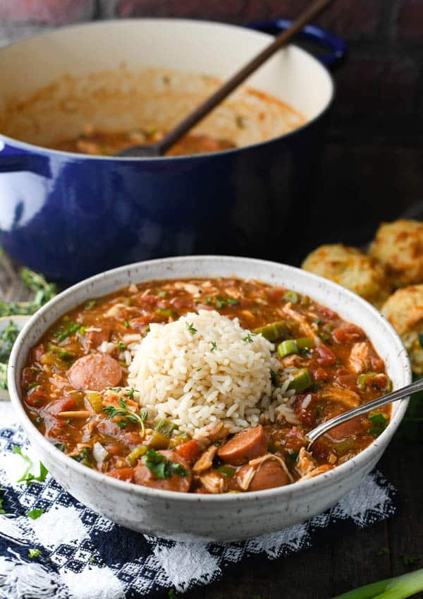 An easy gumbo recipe served in a bowl with white rice and parsley garnish on top