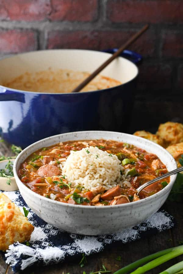 Side shot of a bowl of chicken and sausage gumbo with rice in front of a blue Dutch oven