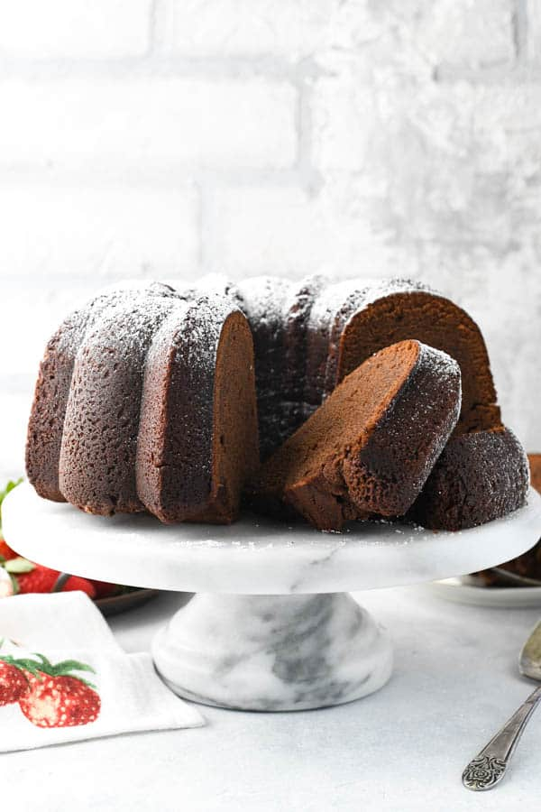 Front shot of sliced chocolate pound cake on a white cake stand