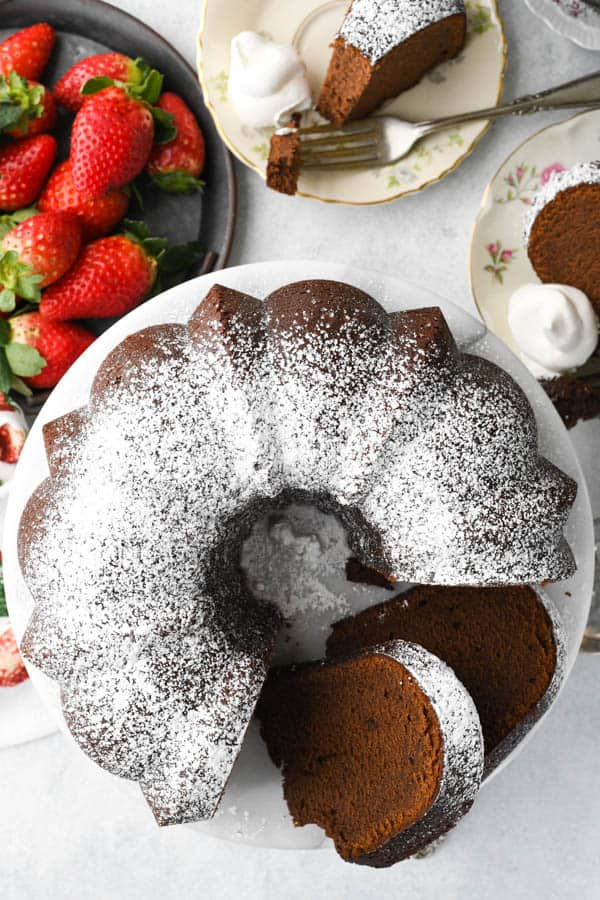 Overhead shot of sliced chocolate pound cake on a white cake stand