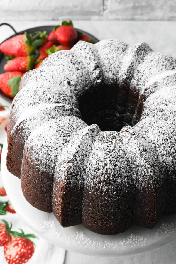 Close overhead image of a traditional chocolate pound cake recipe dusted with powdered sugar