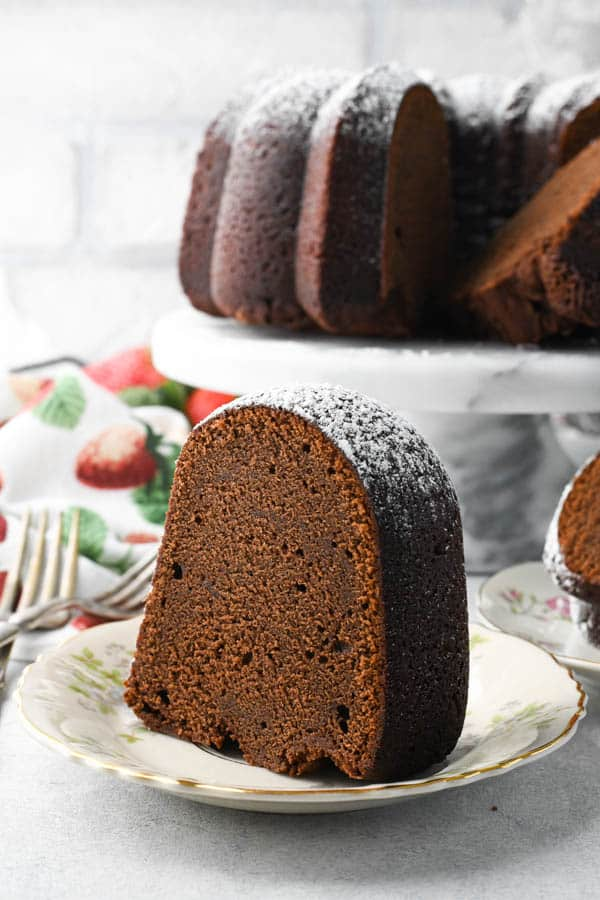 Side shot of a slice of moist chocolate pound cake on a plate