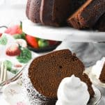 Front shot of a slice of Southern chocolate pound cake recipe on a small plate with whipped cream and strawberries