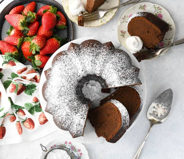 Horizontal overhead shot of a homemade chocolate pound cake recipe on a white surface with fresh berries