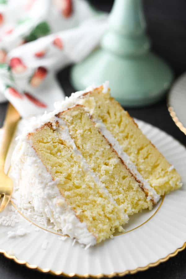Close up shot of a slice of Southern coconut cake on a white and gold plate