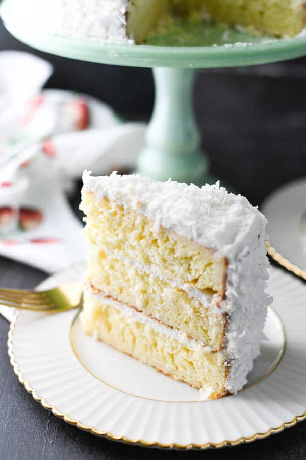 Slice of easy coconut cake on a plate with a gold fork.