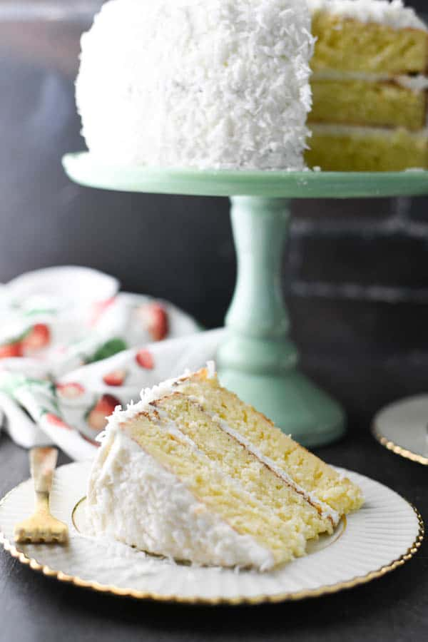 Slice of coconut layer cake on a white plate with a gold trim in front of a green cake stand.