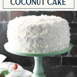 Front shot of the ultimate coconut cake recipe on a green cake stand with text title box at top