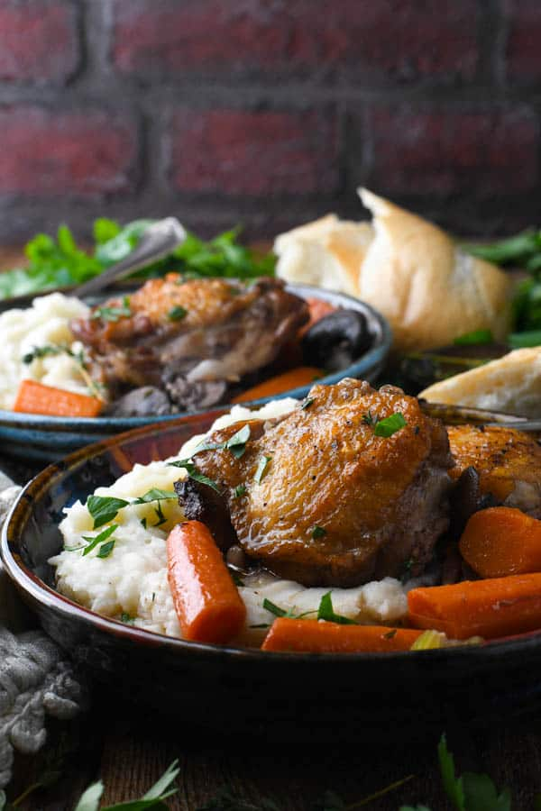 Front shot of two bowls of coq au vin on a table in front of a brick wall