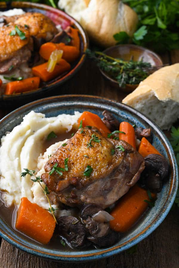Side shot of an easy coq au vin recipe served over mashed potatoes