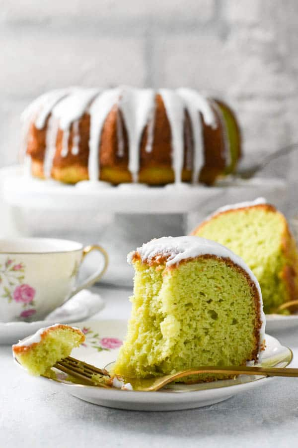 Side shot of a fork taking a bite out of a slice of pistachio pudding cake