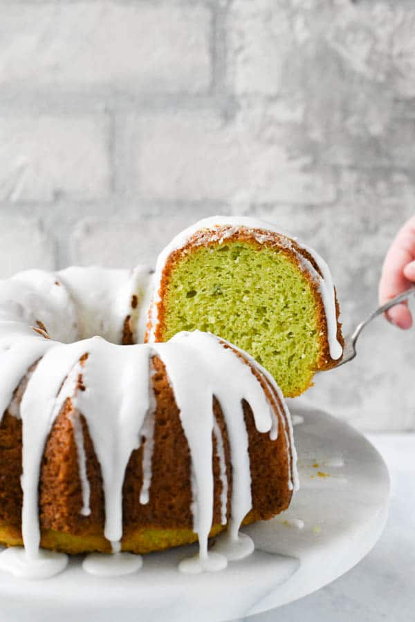 Lifting a slice of the best pistachio cake recipe on a cake server