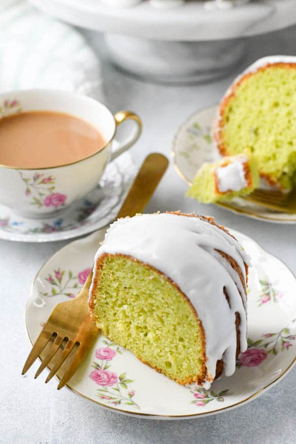 Vintage pistachio cake recipe served on a small floral plate with a cup of coffee