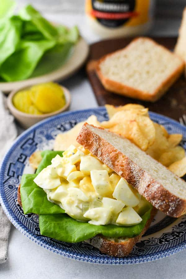 The best egg salad sandwich recipe ever served on white bread with potato chips and pickles on the side