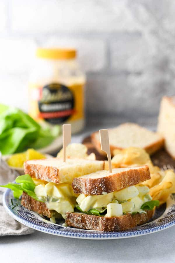 Front shot of classic egg salad sandwich on a blue and white plate with mayonnaise and bread in the background