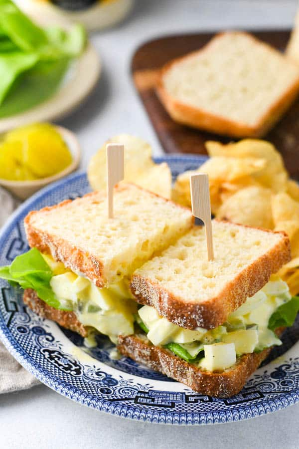 Simple egg salad sandwich served on a plate with potato chips