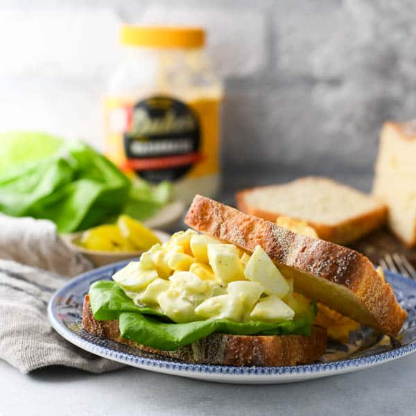Chunky egg salad served on white bread with lettuce