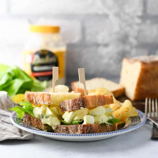 Square shot of an easy egg salad sandwich recipe in front of a white brick wall