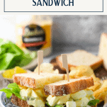 Side shot of a classic egg salad sandwich on a plate with a text title box at the top