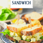 Side shot of an egg salad sandwich on a blue and white plate with text title overlay