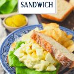 Egg salad sandwich on a plate with text title overlay