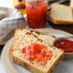English muffin toasting bread on a plate with butter and jam
