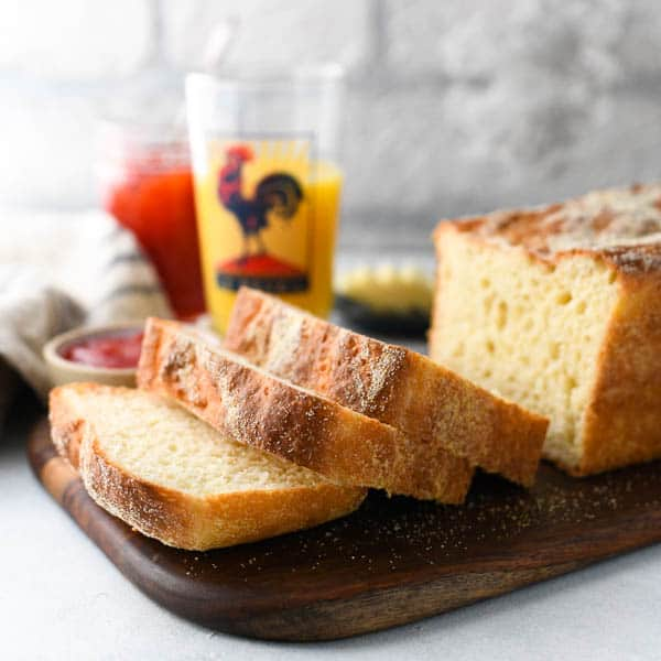 Square image of English Muffin bread recipe sliced and served with butter and jam