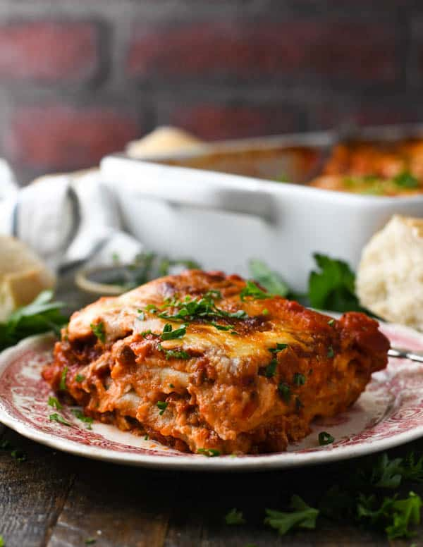Side shot of homemade lasagna with sausage and beef on a plate in front of a brick wall