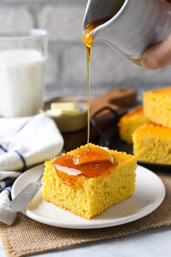 Side shot of pouring honey on a square of homemade buttermilk cornbread