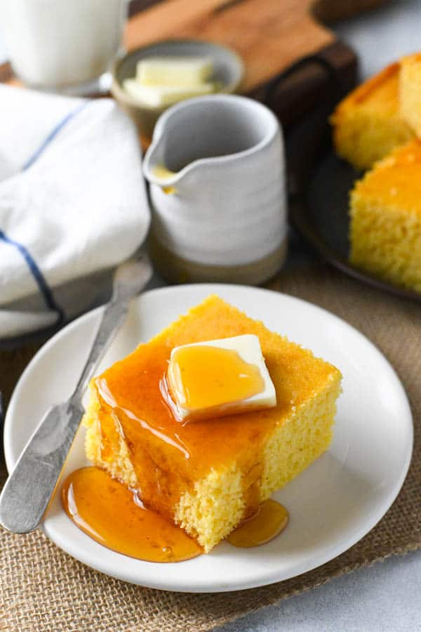 A slice of honey cornbread on a plate with a pat of butter