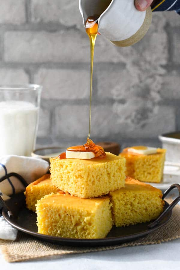 Pouring honey on homemade squares of buttermilk cornbread