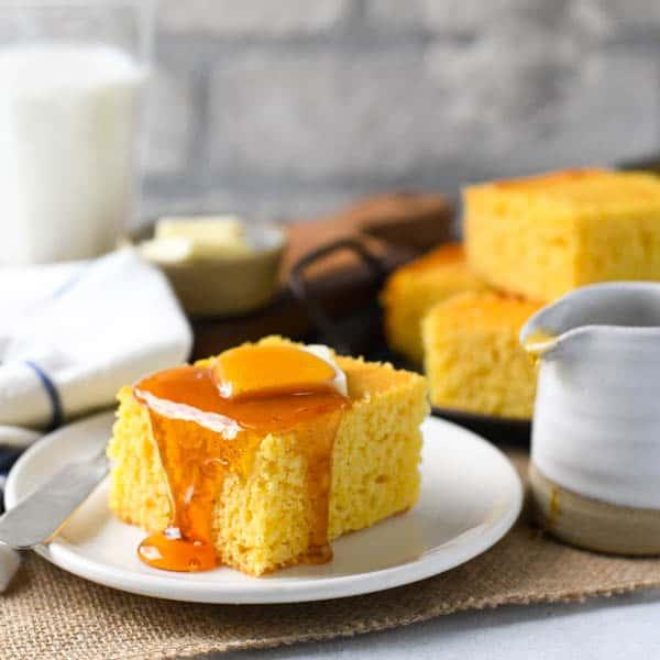Square image of buttermilk honey cornbread on a plate