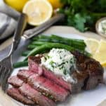 Sliced filet mignon on a plate with garlic herb butter