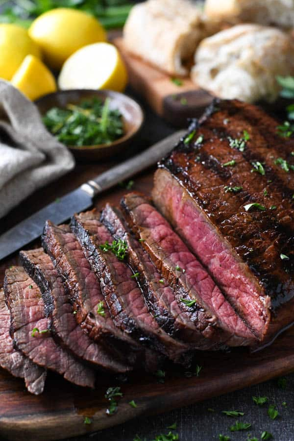 Marinated london broil on a cutting board with fresh herbs
