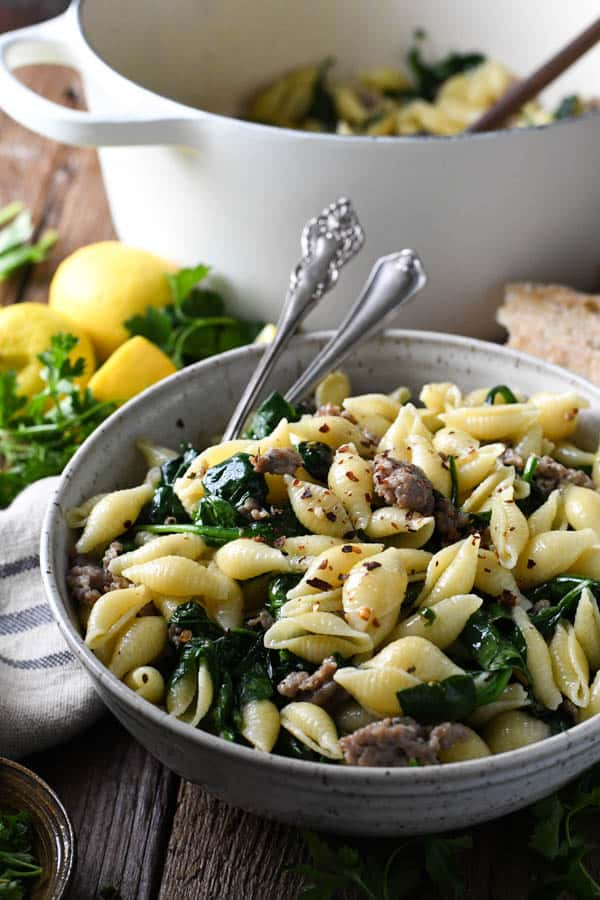Side shot of cheesy pasta with sausage and spinach in a white bowl on a wooden table