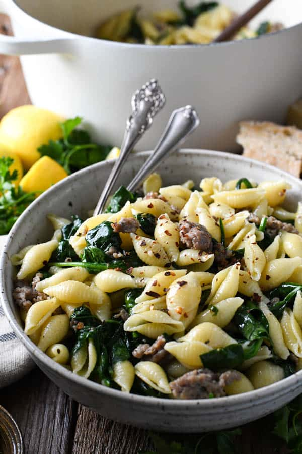 Side shot of pasta with crumbled sausage and spinach in a bowl