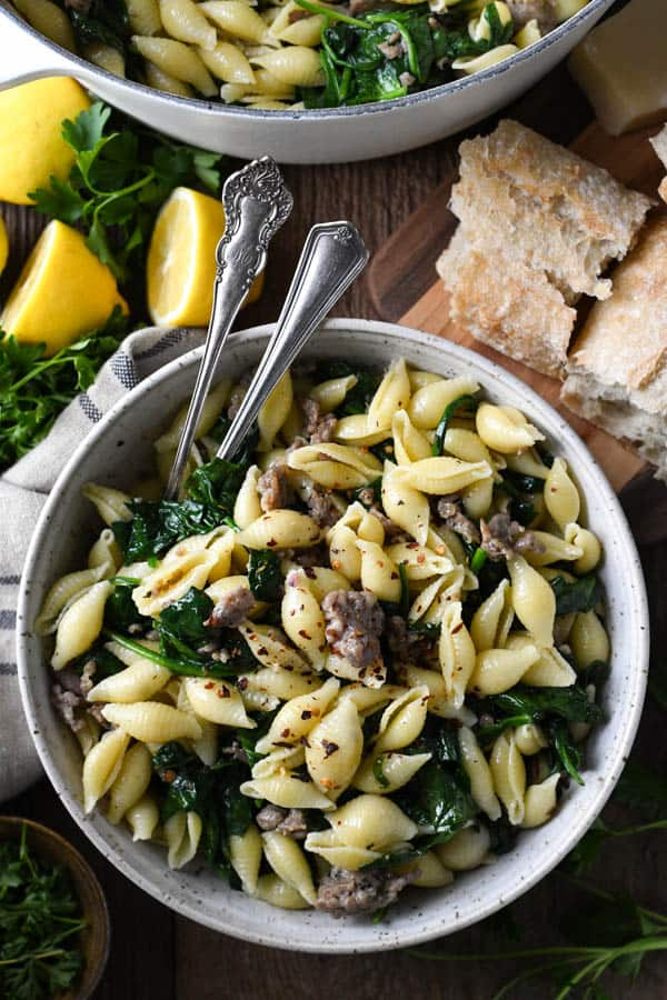 Overhead image of pasta with sausage and spinach in a white ceramic bowl on a wooden table